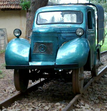 old blue car retrofitted with rail wheels
