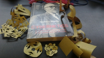 paper curlicues and other papercraft surrounding a copy of Norbert Wiener's Cybernetics