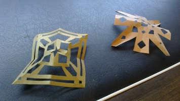 two snowflakes made out of gold paper