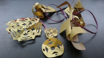 several snowflakes made out of gold paper, plus some scrap gold paper, plus a purple ribbon